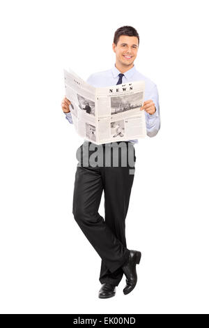 Full length portrait of a handsome man holding a newspaper and leaning against a wall isolated on white background - Stockfoto