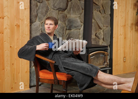 one adult man relaxing in robe and reading newspaper by fireplace with coffee mug - Stock Photo