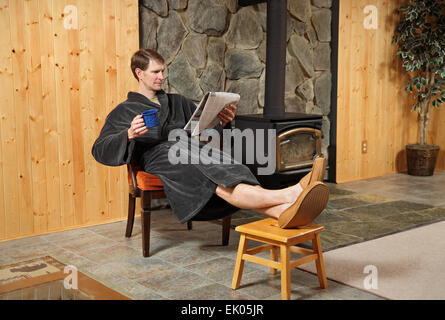 one adult man relaxing in robe and reading newspaper with feet up - Stock Photo
