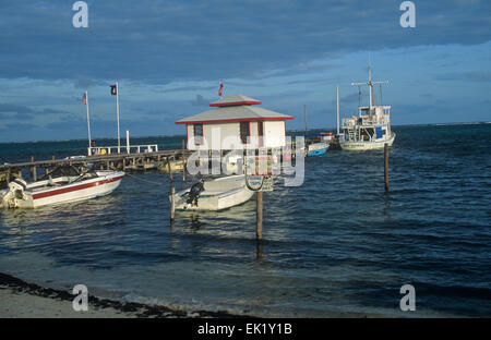 Belize ambergris caye fishing boats tied to wooden dock for Fishing san pedro belize