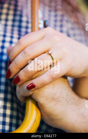 An engaged couple's hands holding an umbrella together. The woman is wearing an engagement ring. - Stock Photo