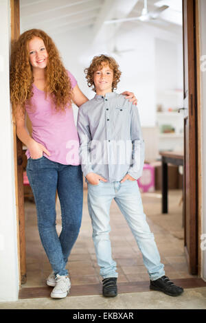 Siblings leaning against wall at entrance - Stock Photo