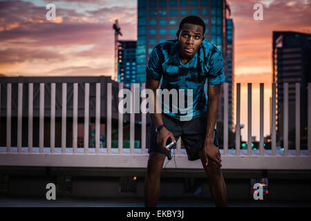 Young male runner taking a break on city roof at sunrise - Stock Photo