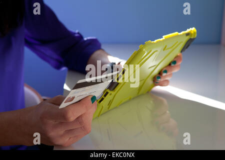 Cropped shot of woman making payment using credit card and digital tablet - Stock Photo