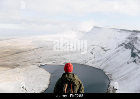 Rear view of man looking at Llyn y Fan Fach, The Brecon Beacons, Wales, UK - Stock Photo