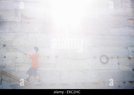 Boy climbing along wall - Stock Photo
