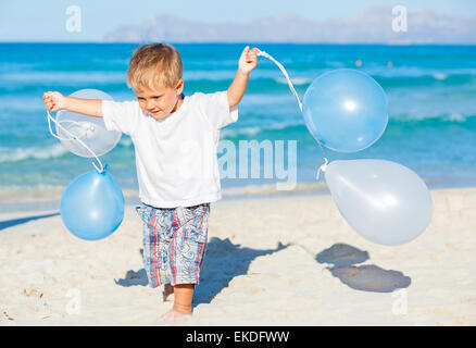 boy plays with ballons on the beach - Stock Photo