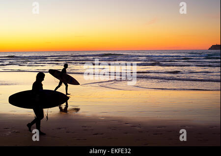 Two surfers running on the beach at sunset. Portugal has one of the best surfing scenes in Europe - Stock Photo