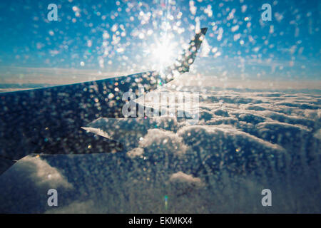 View of airplane wing  and clouds from inside cabin on sunny day with ice on the window. - Stock Photo