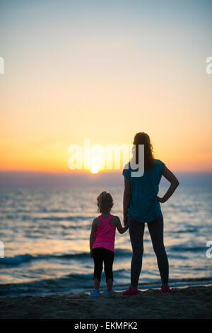 Silhouette of mother and baby girl on beach looking into distance. rear view - Stock Photo