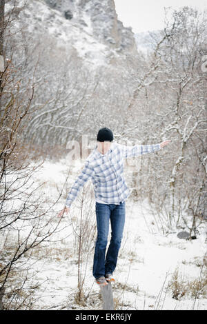 A man in the mountains in winter, balancing on a wood post in the woodland. - Stock Photo