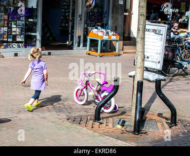 A young blonde girl with a bright pink bike walks back towards her parents who are eating in a sidewalk cafe. - Stock Photo