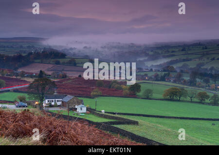 Evening mist lies under on green fields, undulating hills & in the valley, seen from a high viewpoint on Baildon - Stock Photo