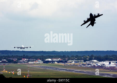 Airbus A380 landing while Airbus A400M Atlas takes off for a display at Farnborough International Airshow 2015 - Stock Photo