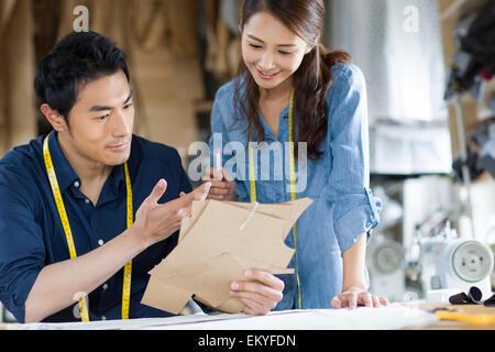 Two fashion designers working in studio - Stock Photo
