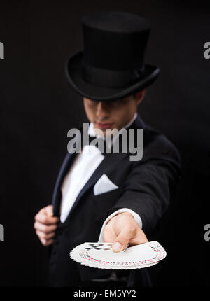 magician in hat showing trick with playing cards - Stock Photo