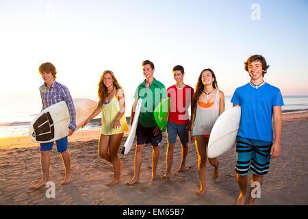 Surfer teen boys girls group walking on beach - Stock Photo