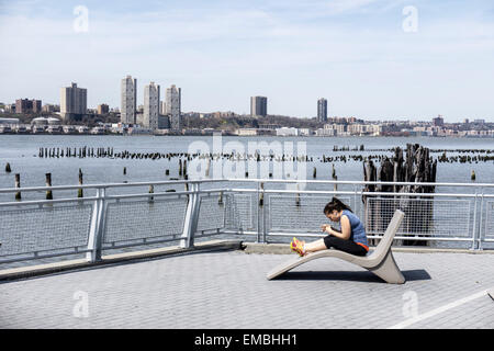 New York City, USA. Sunday April 19, 2015, USA; woman enjoys spring Sunday sitting on permanent outdoor chaise longue - Stock Photo