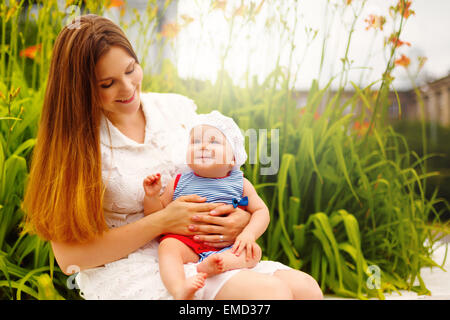 Cute smiling Toddler Baby sitting on Mom`s knees and having Fun. Relaxing in green summer Park. Selective focus. - Stock Photo