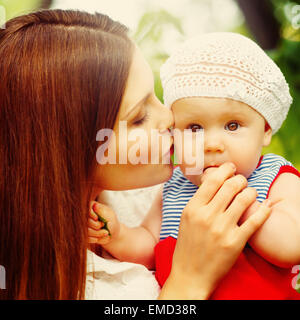 Surprised Toddler Baby Girl sitting on Mom`s Hands, looking into camera. Mother kissing the kid. Relaxing in green - Stock Photo