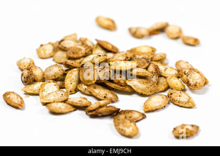 Roasted butternut squash seeds on white background - Stock Photo