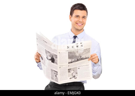 Handsome man holding a newspaper and leaning against a wall isolated on white background - Stock Photo