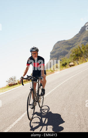 Shot of a male cyclist riding down a country road. Triathlete cycling on a bicycle. - Stock Photo