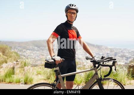 Portrait of fit young man standing with his bicycle, outdoors. Taking a break after a cycling training session. - Stock Photo