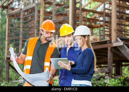 Engineers Using Digital Tablet At Construction Site - Stock Photo