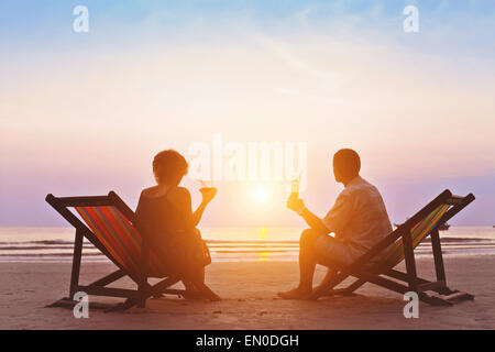 family enjoying romantic sunset on the beach - Stock Photo