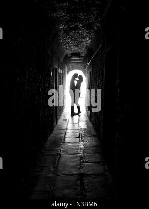 Italy, Venice, Young couple kissing in archway - Stock Photo