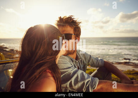 Affectionate young couple kissing at the beach. Loving young couple with sea shore in background. Romantic couple - Stock Photo