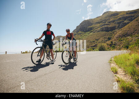Two young athletes taking a break from cycling on country road. Cyclist training for triathlon competition on open - Stock Photo
