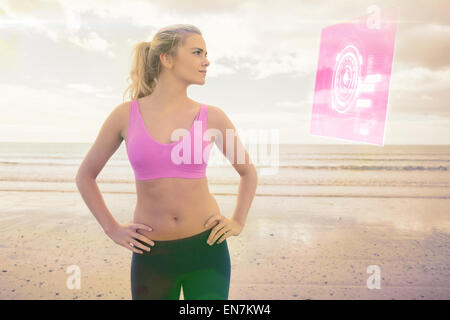Composite image of toned woman with hands on hips on beach - Stock Photo