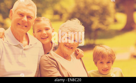 Smiling senior couple and grandchildren at park - Stock Photo
