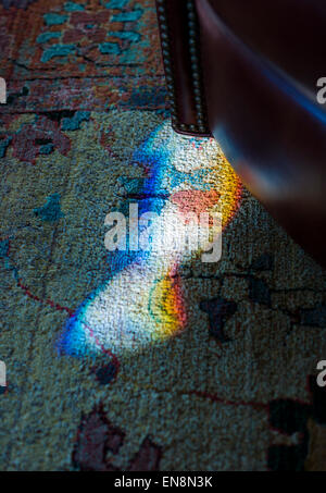 Late day sunlight refracted through a stained, leaded glass window creates a prism of color on carpeting - Stock Photo