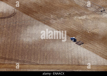 An aerial view of a tractor plowing a field in preparation for planting. - Stock Photo