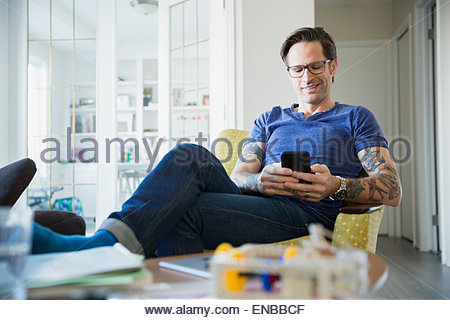 Relaxed man with tattoos texting in living room - Stock Photo