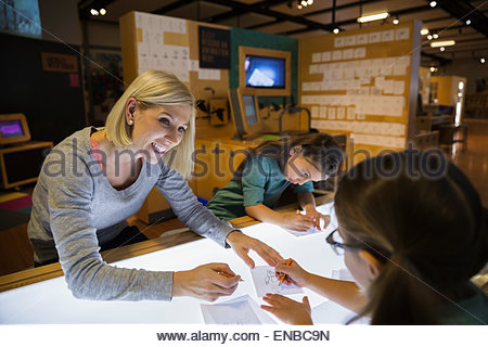 Family tracing on light table at science center - Stock Photo