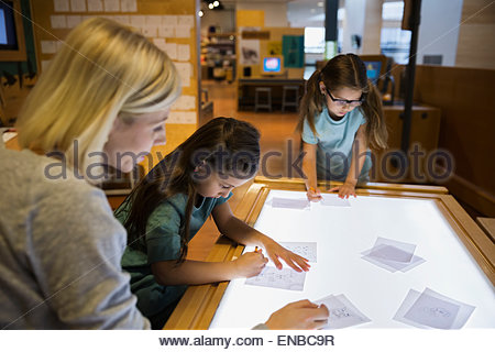 Family tracing on light table at science center - Stockfoto