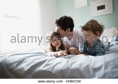Father and children using digital tablet in bed - Stock Photo
