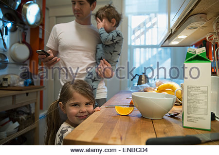 Portrait of smiling girl in kitchen at breakfast - Stock Photo