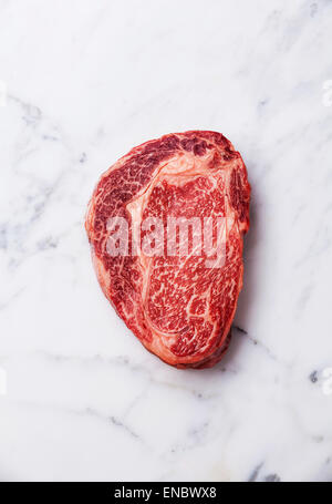 Raw fresh marbled meat Black Angus Steak Ribeye on white marble background - Stock Photo