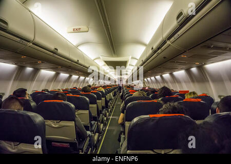 Commercial airliner interior economy class cabin - Stock Photo
