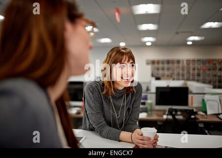 Two women seated in an office talking. - Stock Photo