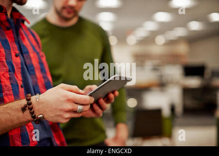 Two men looking at a digital tablet screen. - Stock Photo