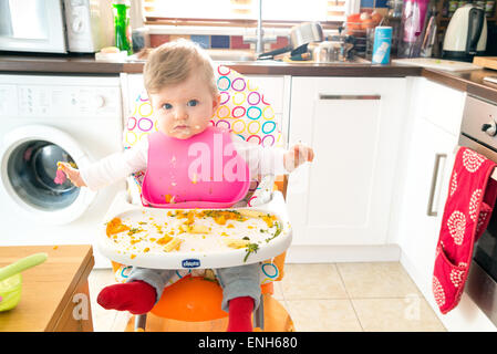 Baby led feeding a six month old baby eating messily - Stock Photo
