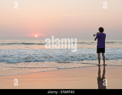 A man playing a trumpet on Agonda beach in Goa South India at sunset - Stock Photo