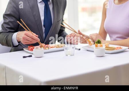 close up of couple eating sushi at restaurant - Stock Photo