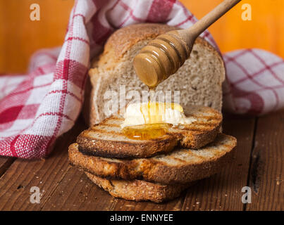Toasted bread with honey and honey dipper on a wooden background. - Stock Photo